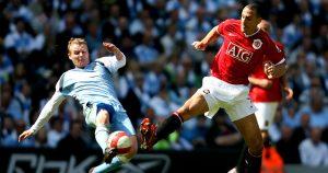 Manchester City's Michael Ball tackling Rio Ferdinand
