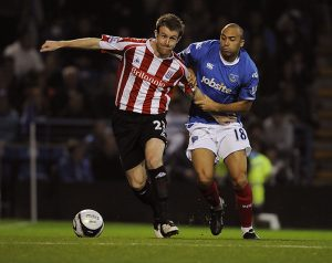 Portsmouth's Anthony Vanden Borre (right) and Stoke City's Michael Tonge (left) battle for the ball.