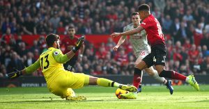 Jesse Lingard of Manchester United attempts to go round Alisson of Liverpool