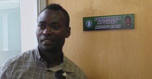 Tonton Zola Moukoko outside the meeting room named after him at Sports Interactive's studios
