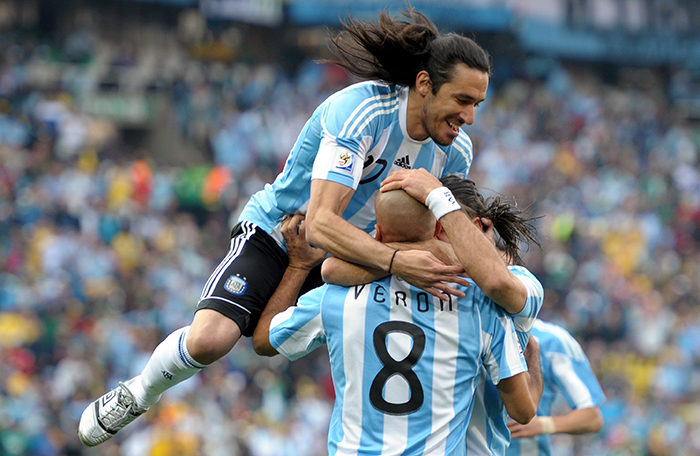 Jonas Gutierrez (top) and Juan Veron of Argentina celebrate the opening goal against Nigeria as the mob goalscorer Gabriel Heinze (hidden)