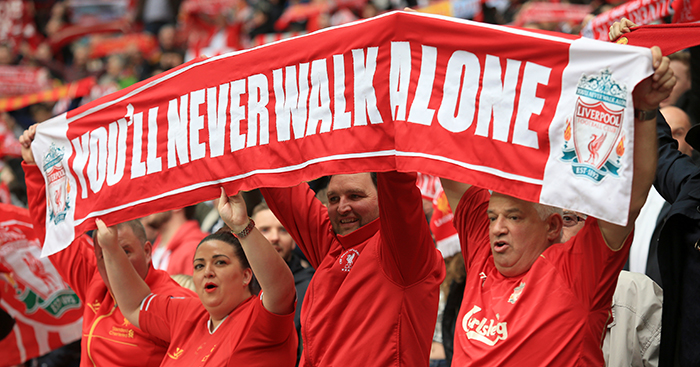 Liverpool fans hold up a banner which reads You'll Never Walk Alone
