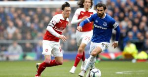 Arsenal's Mesut Ozil (left) and Everton's Andre Gomes battle for the ball