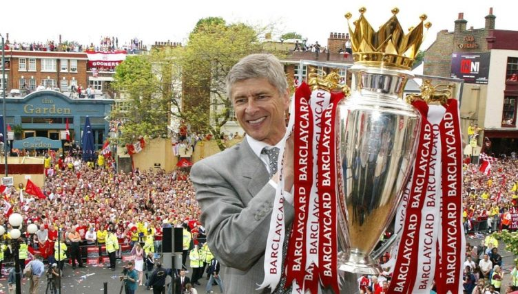 Arsene Wenger holds the Premier League trophy during Arsenal title parade in 2004.