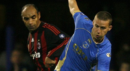 Portsmouth's Sean Davis and AC Milan's Emerson battle for the ball.