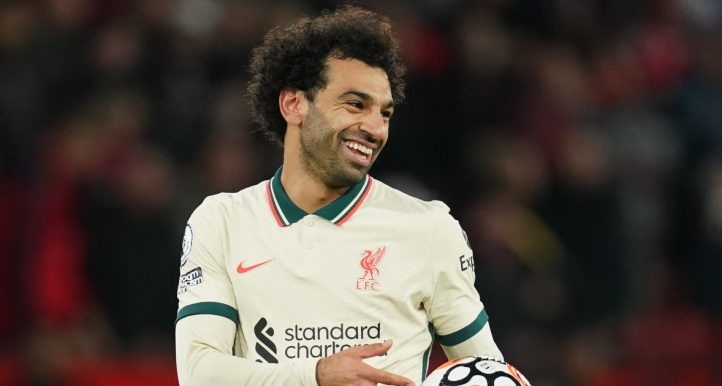 Liverpool's Mohamed Salah celebrates with the match ball after scoring a hat-trick against Manchester United.