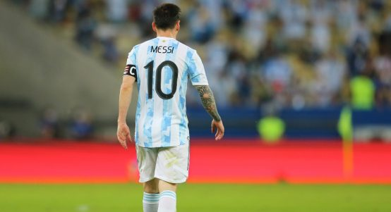 Lionle Messi in a light blue and white Argentina No.10 shirt walking across the pitch with his back turned to the camera. Maracana July 2021.