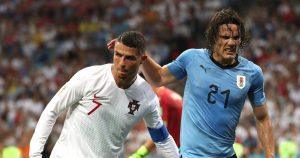 Cristiano Ronaldo helps Edinson Cavani off the pitch.