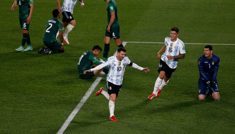 Lionel Messi celebrates with his arms open as Bolivia players sit on the floor.