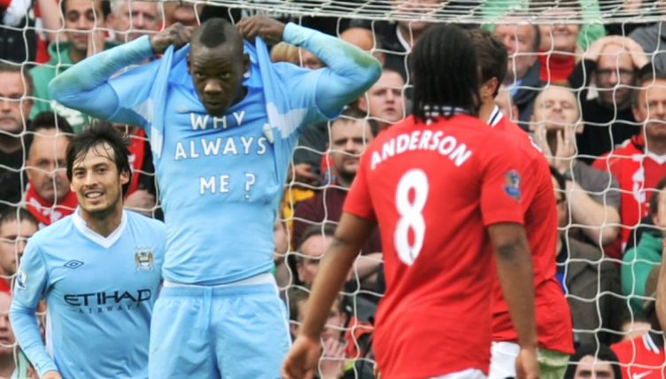 Mario Balotelli celebrates scoring against Manchester United by revealing a t-shirt with 'Why Always Me?' written on it.