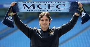 Roque Santa Cruz holding up a Manchester City scarf at the City of Manchester Stadium, July 2009.