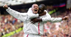 David Beckham celebrates scoring a freekick against Greece at Old Trafford alongside Emile Heskey, October 2001.