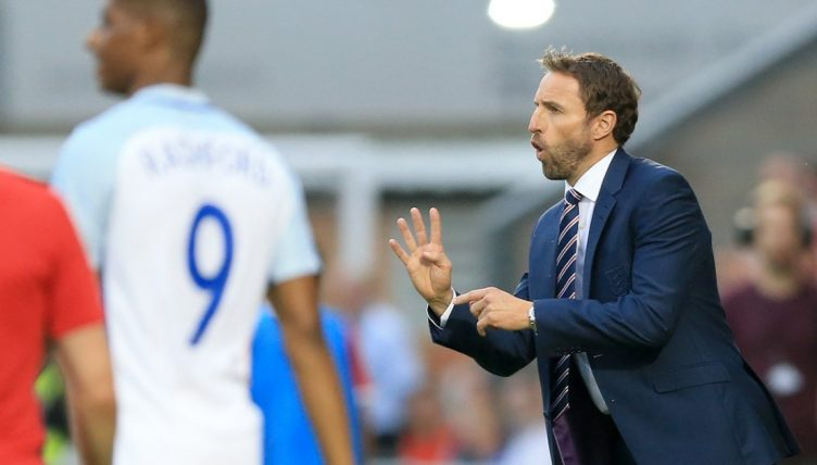 England U21 manager Gareth Southgate holds up four fingers while shouting instructions at his players.