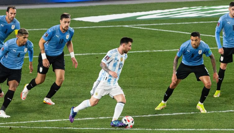 Uruguay defenders keep a close eye on Argentina's Lionel Messi
