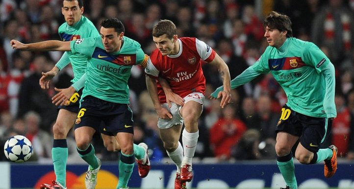 Jack Wilshere is marked by Xavi and Lionel Messi as Arsenal play Barcelona at the Emirates Stadium. February 2011.