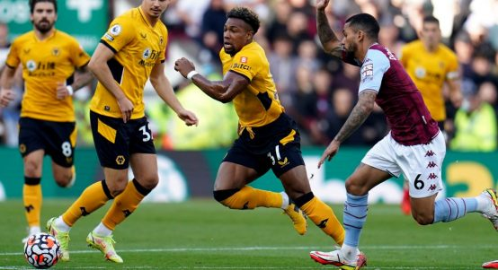 Wolves' Adama Traore dribbles away from Aston Villa's Douglas Luiz. October 2021.