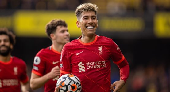 Liverpool's Roberto Firmino celebrates with the match-ball after completing his hat-trick.